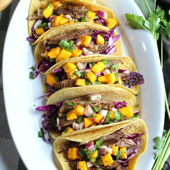 Steak Taco topped with a delicious mango jalapeño salsa laid on a bed of shredded purple cabbage!