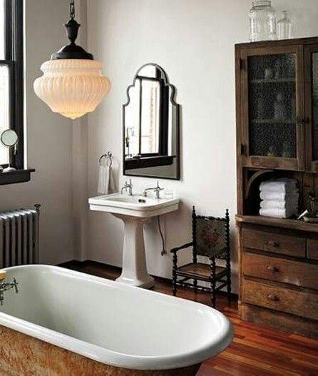 Farmhouse bathroom - like copper bath, vintage dresser, grand pendant.