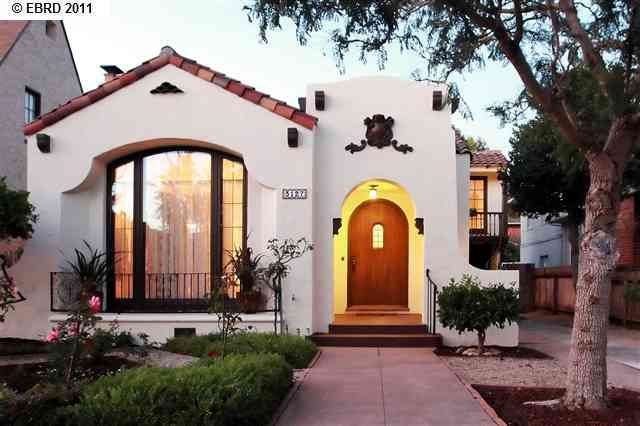 Spanish bungalow. Metal accents, wood door, light in entryway.