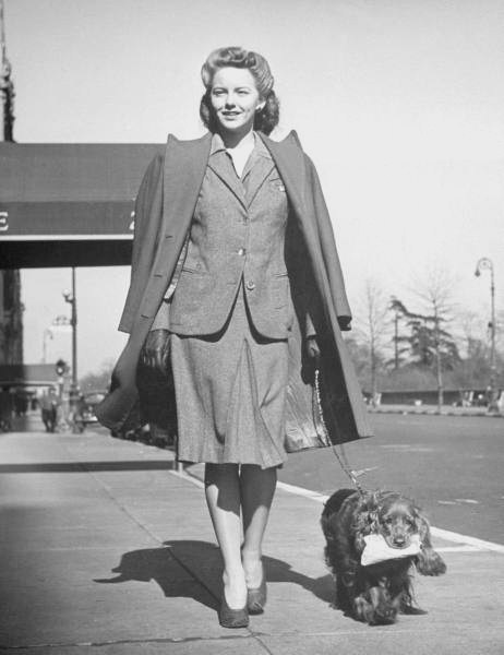 Model Mimi Berry walking her cocker spaniel, who is carrying a package for her in its mouth-NYC - Photo by Nina Leen - 1944