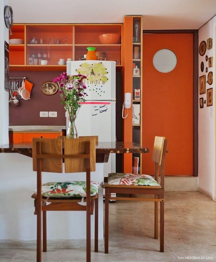 cozinha laranja e integrada com piso de cimento queimado