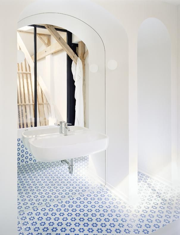 STILE COUNTRY IN GERMANIA: GIOCHI DI RIFLESSI Un mosaico di ceramiche a decori floreali blu e bianchi riveste il pavimento del bagno, mentre uno specchio montato in un arco riflette la luce che proviene dal lucernario aperto sopra la zona giorno.