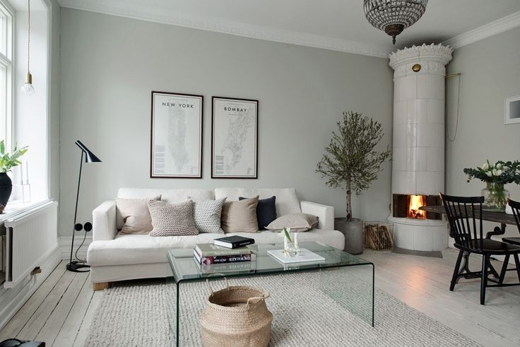Living room with greige walls, white pigmented floor and an old-fashioned fireplace. White couch with beige and grey cushions, transparent coffee table, floor lamp by Louis Poulsen and city map posters.