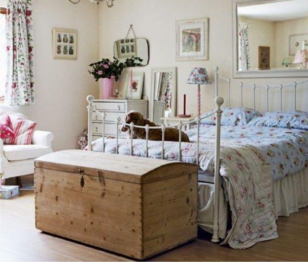 Piccola camera con arredi in stile rustico - Letto in ferro battuto bianco, baule di legno e credenza capiente per arredare una piccola camera da letto.
