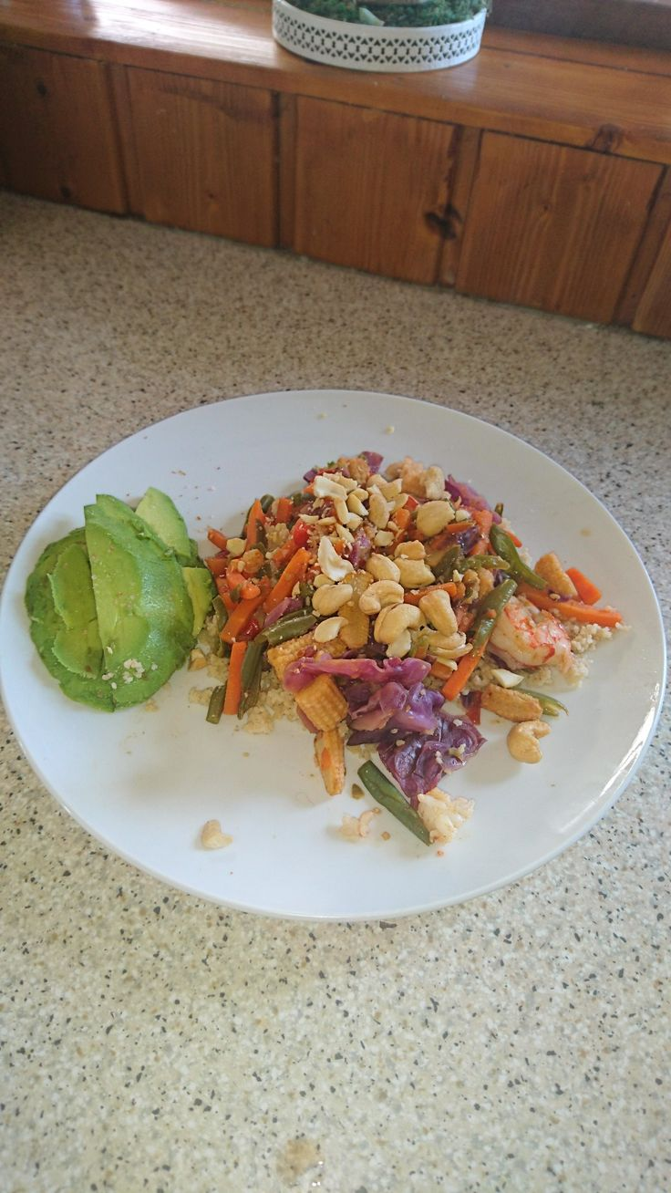 Chicken stir-fry on a bed of cous cous topped with cashews and avo