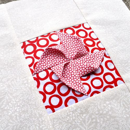 Detail of origami pinwheel Block type: log cabin Block size: 11 inches Colour scheme: reds and neutrals Texture/fabric manipulation: fabric folding / fabric origami Quilt size: The finished quilt i…