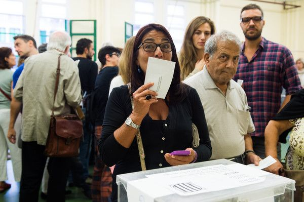A woman kisses her ballot before casting her vote on September 27, 2015 in Barcelona, Catalonia. The main Catalanist parties, Catalan Democratic Convergence 'Convergencia Democratica de Catalunya' party (CDC), Republican Leftist of Catalonia 'Esquerra Republicana de Catalunya' party (ERC) and a group of social associations have joined together to form a Catalan pro-independence coalition 'Junts pel Si' (Together for the Yes).