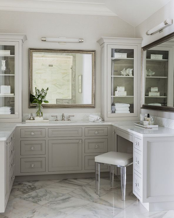 Absolutely stunning bathroom features a gray built-in vanity topped with white marble paired with a lucite vanity stool under an antiqued nickel vanity mirror illuminated by a long sconce atop marble tiles laid out in a diamond pattern.
