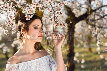 almond flowers: Ritratto di giovane donna nel giardino fiorito in primavera. Mandorle fiori fiori. Ragazza vestita di bianco come una sposa.