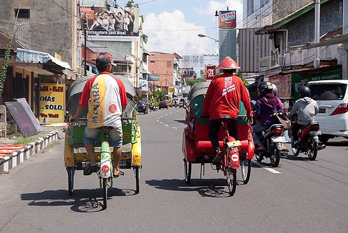 Becak (people driven cabs) on the streets of Solo along with the motorbikes and cars.