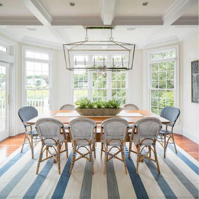 This Coastal Dining Area Features A Darlana Linear Chandelier From Visual Comfort And Bistro Chairs