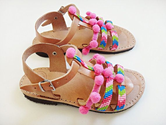 Strawberry Pom Pom Candy Gladiators Sandals for Kids and Baby girls in natural leather color. Handmade strappy leather sandals adorned with fuchsia