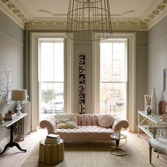 I love the contrast of the classic architecture & sofa against the rustic number wall hanging and metal cage pendant light. | Mad About The House