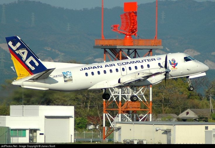 Japan Air Commuter-JAC Saab 340 JA8703 aircraft, with the stickers ''Nishi Hiroshima'' & the ''Ruri'' mascot on the airframe, in old livery, landing at Japan Kagoshima International Airport. 17/04/2005. (Nishi Hiroshima=Nishi Ku=one of 8 wards in the city of Hiroshima).