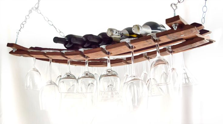 Made from recycled oak wine barrel staves, this hanging wine rack is a favorite among wine enthusiasts and is sturdy enough to hold up to 5 bottles of wine and 21 wine glasses. They're ideal for adding a warm pub, vino-culture, or nautical touch to any room. This rack is also a unique conversational piece that will make your next gathering an impressive one.  10 foot hanging chain included.  Ceiling hooks not included.   Oversize item, handling fee shown in cart.