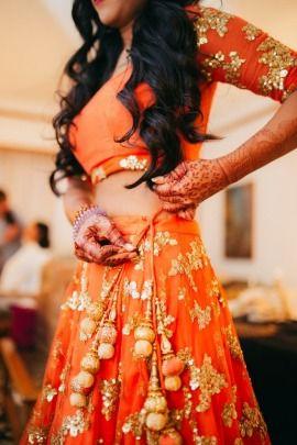 Bridal Details - Filip & Tuhina wedding story | WedMeGood | Orange Lehenga with Orange and Beige Pom Poms #wedmegood #indianbride #bridaldetails #orange #lehenga
