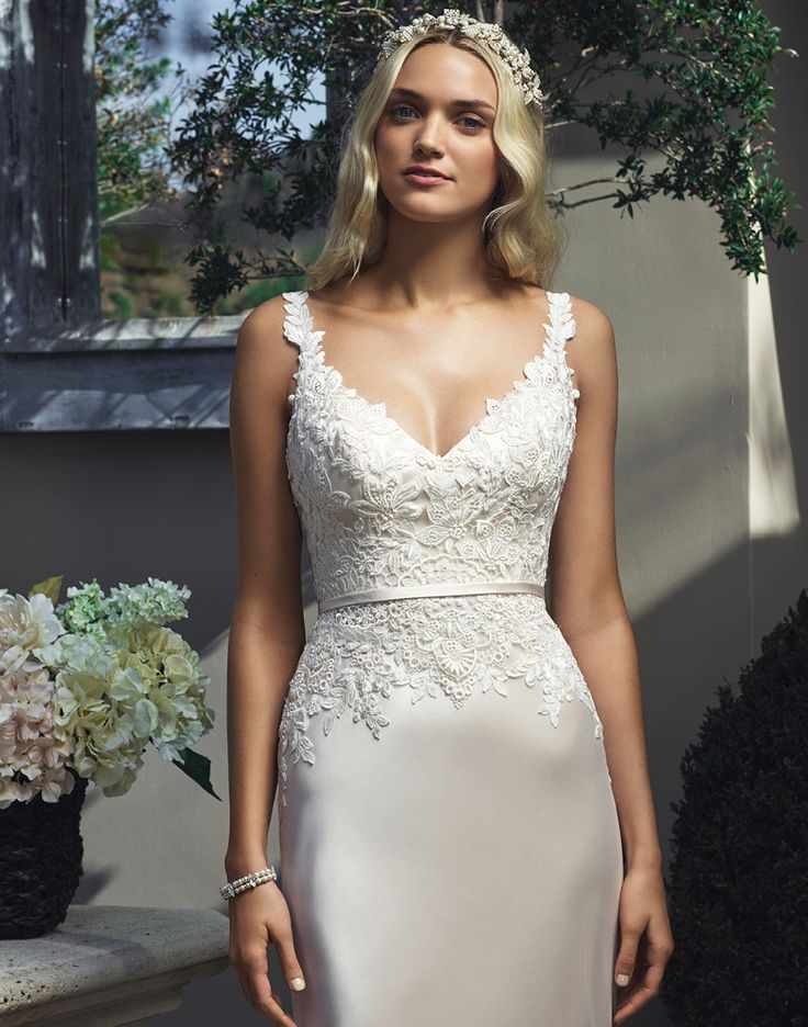 This luxe silk charmeuse Casablanca 2210 wedding dress brings a touch of Hollywood glam to your special day. Lacey straps embrace the shoulder and give way to a deep V-neckline. Lace applique tops the bodice and spills down the hip while the natural waistline is accentuated by thin satin waistband. The open backline harkens to lingerie, while a lace trimmed tulle overlay finishes to a dramatic round puddle train.