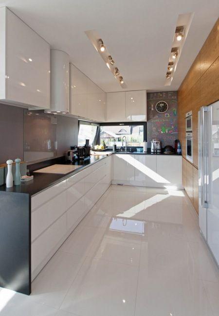 Białe szafki z połyskiem podkreślają nowoczesny stylu kuchni. Farba tablicowa na ścianie w głębi pomieszczenia dekoruje wnętrze oraz pełni także praktyczną funkcję. Czarne blaty na zasadzie kontrastu ożywiają aranżację.