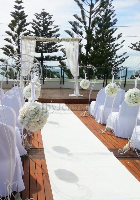 All white wedding ceremony with single arch with flower garland, ornate shepherds hooks with rose balls and white carpet - Decorations by Jelena