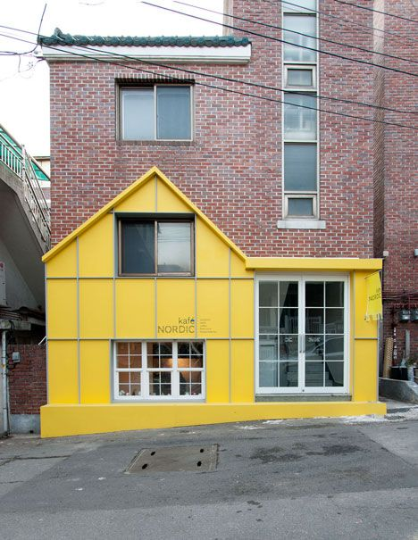 The bright yellow facade of this cafe in Seoul references the exterior of a Scandinavian house