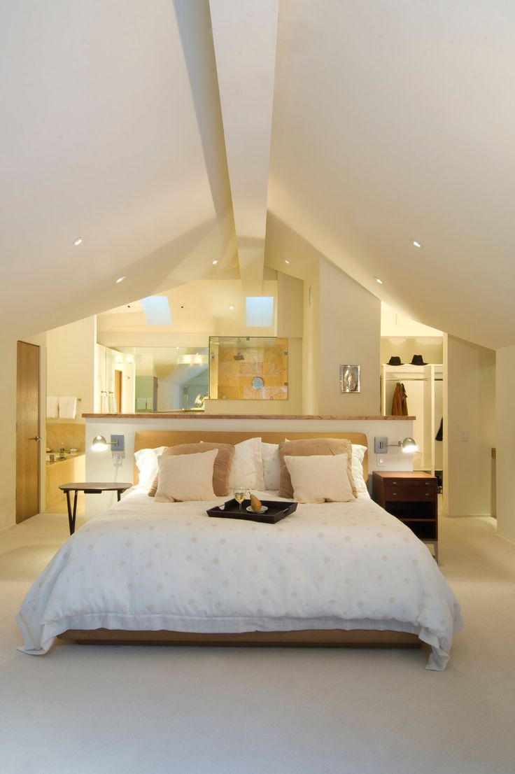 An open concept attic space houses a bedroom, closet, and bathroom. The bed is situated against a half-wall, creating a separate-yet-together feeling to this attic apartment.