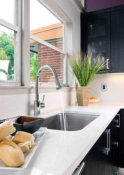A Caesarstone white countertop and white porcelain tile backsplash create a clean working surface that also contrasts dark walnut cabinetry. This undermount Franke sink and single-lever faucet keep the look minimal and sleek.