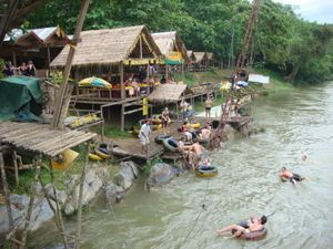 Tubing in Vang Vieng with a bottle of Laos beer - good times!