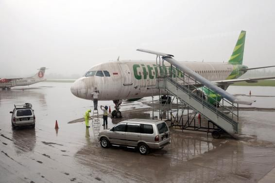 Workers stand near a Citilink airplane covered with ash from Mount Kelud at Adi Sucipto airport in Yogyakarta February 14, 2014. REUTERS-Dwi...