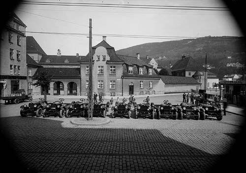 9 personbiler oppstilt utenfor Automobilkompaniet, Nygårdsgaten 13. I bakgrunnen Nygård skole. Fotografi skapt av Atelier KK Oppdragsgiver: Automobil companiet av 1923 Laget mellom 1927-01-01 og 1929-12-31