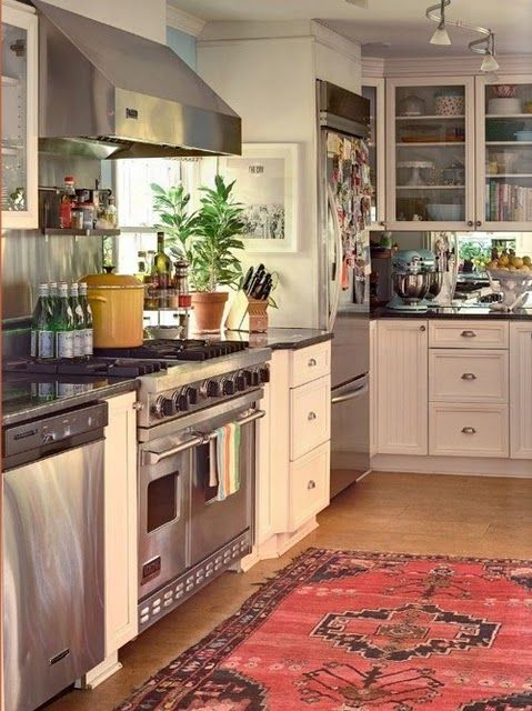 Love the use of an oriental rug, but I don't think I'd ever assume that part of the kitchen would be spill-proof enough for one!