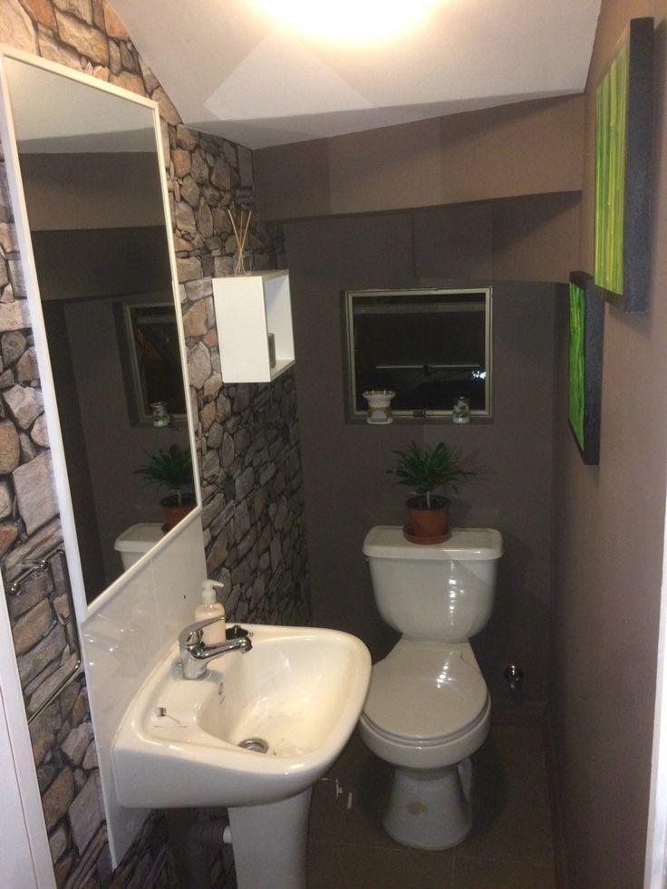 Baño de visitas bajo escalera paredes cafes pared piedra espejo blanco