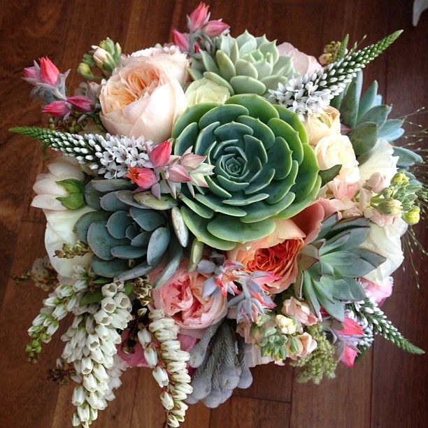 I love so many elements in this bouquet by The Moss & Rose. The succulents and peach colored roses make me drool, and those accents of draping whites are so lovely! Beautiful!