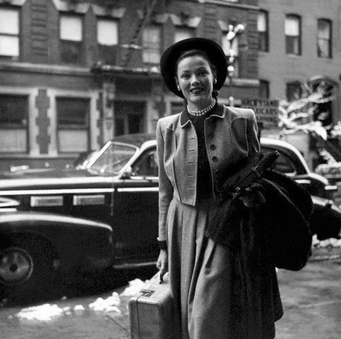 Gene Tierney carries a suitcase as she walks on a city sidewalk photographed by John Rawlings,1946.