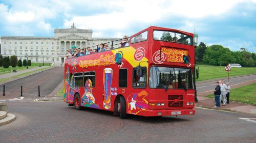 Showing item 1 of 5. Hop on Hop off bus driving past the Northern Ireland Assembly building in Belfast