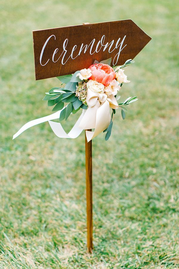 Festooned with beribboned flowers and foliage, a calligraphed wooden arrow pointed the way. | Photo by Tony Gigov