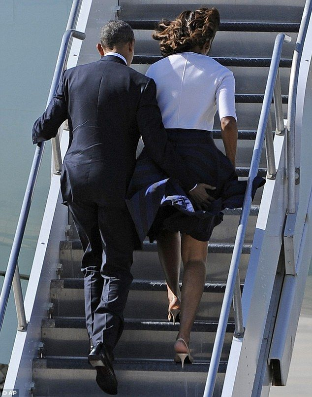 Close call: Barack Obama saved wife Michelle from an embarrassing situation while the two boarded Air Force One today