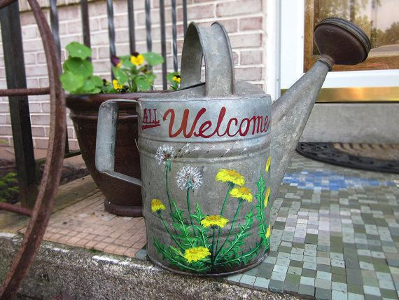 """All Welcome""   This item is a collaboration of husband and wife team Cynthia and Dean (more about them on our website, greaseandgrace.com)  Antique watering can with no holes or cracks, hand lettered (Dean) and hand painted (Cynthia). Delightful dandelion motif cheers up your entryway, stoop, patio or potting shed. Gorgeous as decor or even a planter. : $80.00"