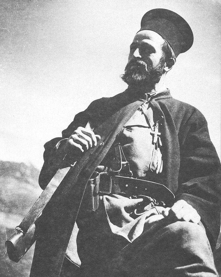 """Ο πρωτοπρεσβύτερος Δημήτριος Κ. Χολέβας (26 Ιανουαρίου1907 - 16 Ιουλίου 2001), πιο γνωστός ως Παπαχολέβας, ήταν ιερέας, φιλόλογος, ιστορικός, αρχαιολόγος και μέλος του Ελληνικού Λαϊκού Απελευθερωτικού Στρατού (ΕΛΑΣ), με το ψευδώνυμο """"Παπαφλέσσας"""", κατά την διάρκεια της Εθνικής Αντίστασης. Απαθανατίστηκε σε φωτογραφία του Σπύρου Μελετζή ως σύμβολο των «φλογισμένων ράσων», του αγέρωχου παπά-αντάρτη της Εθνικής Αντίστασης"""" (Wikipedia). Φωτ. Σπύρος Μελετζής. Πηγή: www.lifo.gr"""