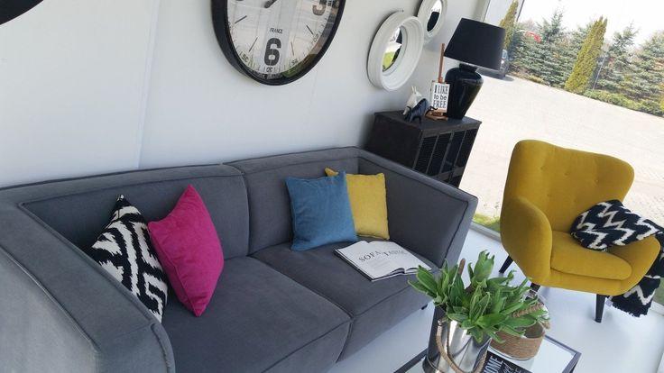Tapicerowana sofa o niewielkim rozmiarze w kolorze szarości. Urozmaicona kolorowymi poduszkami z pewnością doda uroku każdemu wnętrzu.