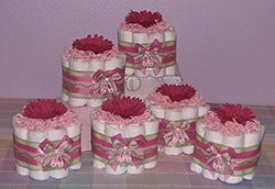 mini diaper cakes centerpieces on a pedistal with real flowers in center?