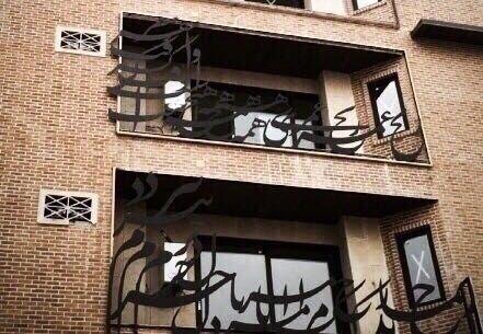"""بيت شعري مسيّج على شُرفة بناية في طهران ترجمته : """"أنتَ يا من تزول هموم العالم بنظرة من عينيك. أسفي أن تكون موجودٌ والهم يسكنني"""""""
