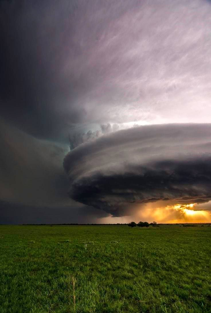Massive supercell storm over this green landscape.