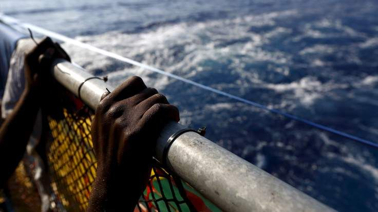 Migrant holds onto a railing at the stern of the Medecins Sans Frontiere (MSF) rescue ship Bourbon Argos somewhere between Libya and Sicily