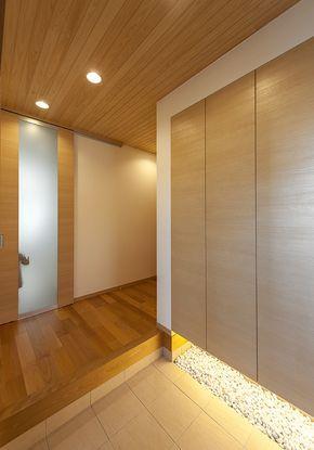 使い勝手の良い引き戸タイプの玄関扉を開けた正面に下駄箱を設置。下駄箱下部は間接照明で敷ならした玉石を照らし、雰囲気を演出。