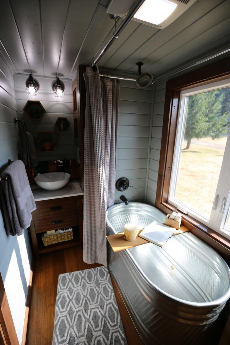 As seen on season 1 of Tiny Luxury, this spacious, spa-like bathroom features a galvanized horse trough soaking tub, vessel sink and lots of natural light.