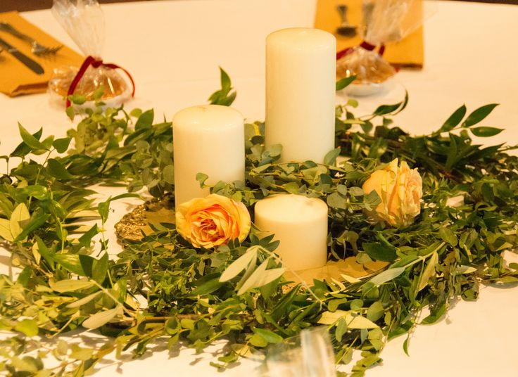 table centerpiece with lots for greenery.  Made of myrtle, eucalyptus and olive branches with garden roses, and pillar candles