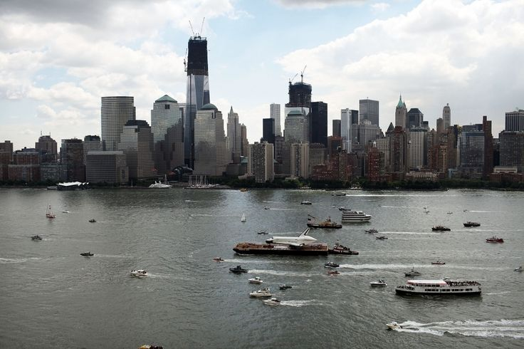 A flotilla surrounds NASA space shuttle Enterprise as it is carried by barge past One World Trade Center up the Hudson River on route to its permanent home at the Intrepid Sea, Air and Space Museum.