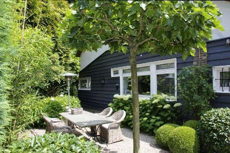 Grijze Muur - Witte Kozijnen - Buxus - Bomen - Rieten Stoelen