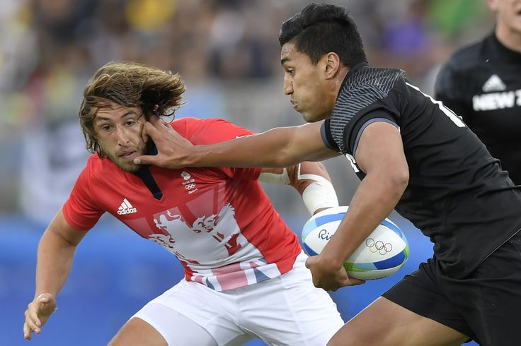 New Zealand's Rieko Ioane hands off Britain's Dan Bibby in the mens rugby sevens match between New Zealand and Britain during the Rio 2016 Olympic Games at Deodoro Stadium in Rio de Janeiro on August 10, 2016. / AFP / PHILIPPE LOPEZ