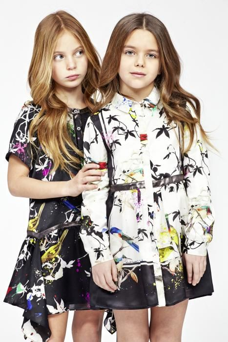 A girl model in a black short sleeve button down bird's garden print dress, next to another girl model in a long sleeve white button down bird's garden dress (link to access the girl's lookbook)